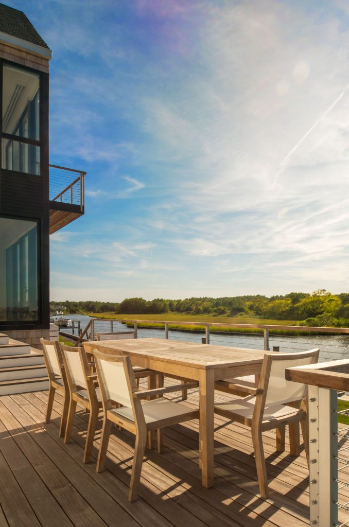Natural decking, lots of glass walls, and minimal cable railing are all that separates  this home from the waters just beyond.