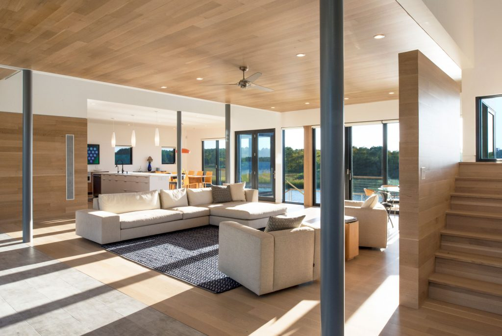 """The living area's intentionally minimalist appearance doesn't spill over into the austere, thanks to subtle """"warming"""" touches like a wood ceiling."""