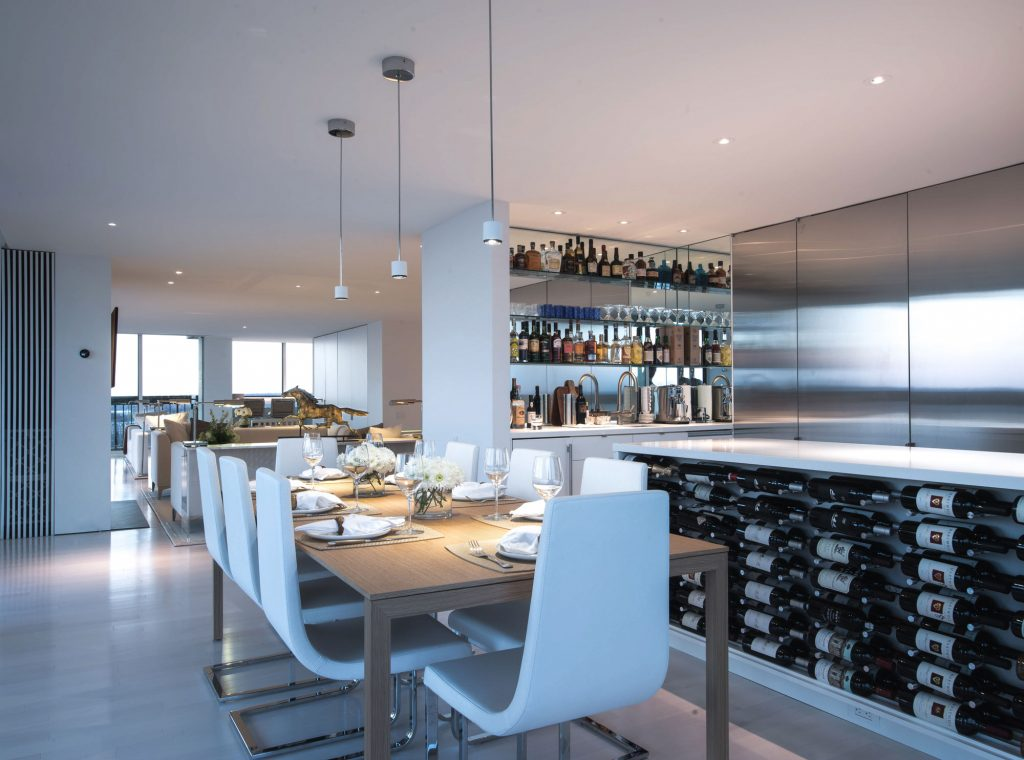 The dining area adjacent to the kitchen maintains the sleek, clean lines of the other public spaces, while adding subtle color and materials choices.
