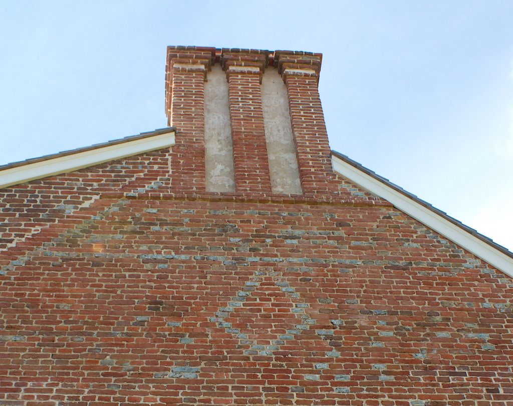 Brick construction was a rarity in 1705 Maryland and houses of Cloverfields' caliber are extraordinary. Seen here are the elaborate triple-stack chimneys and a gable wall accented with silver-gray glazed bricks. The diagonal line of bricks at left shows the break between the 1705 house and 1769 rear second-story addition.