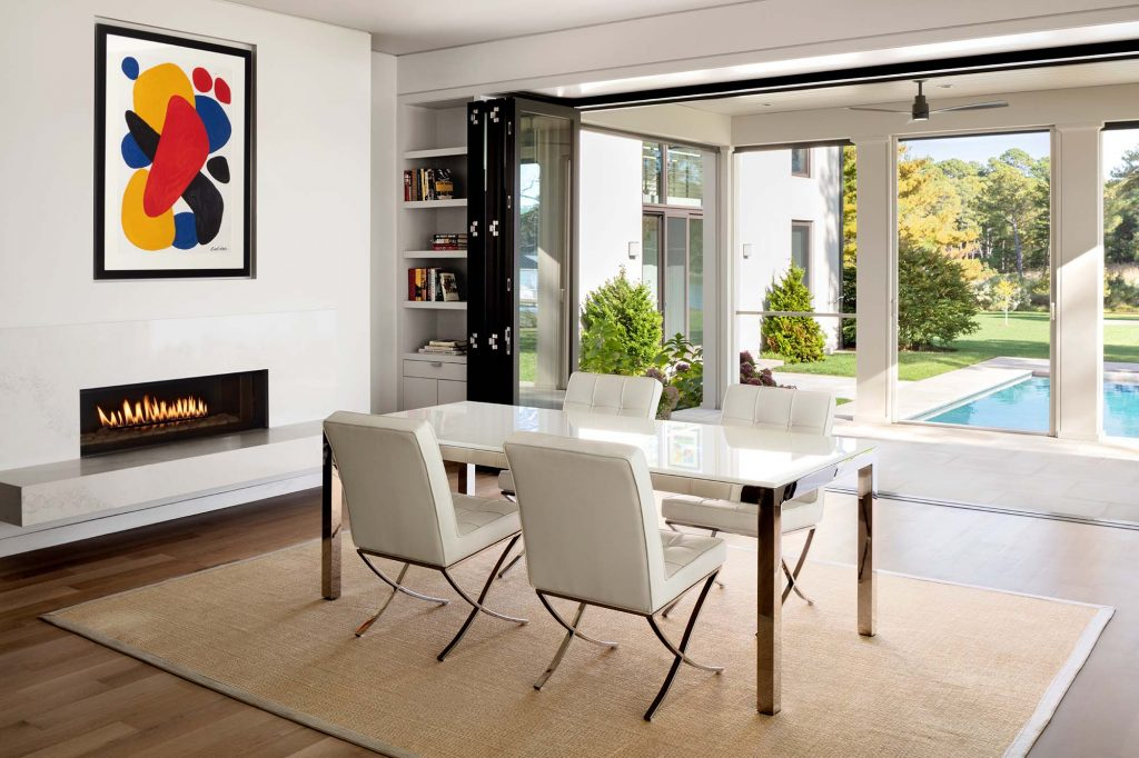 A wall of windows in the dining area slide back so the room opens out to an airy foyer, encouraging connections to land and nature. The wall space above the fireplace was designed specifically for the art.
