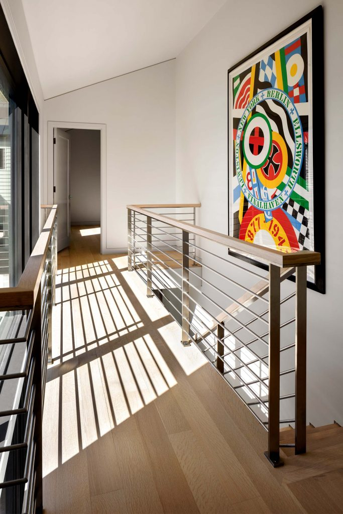 The upper hallway in the guest house, with modern railing and art, leads to separate guest suites, each with a mini-kitchen.