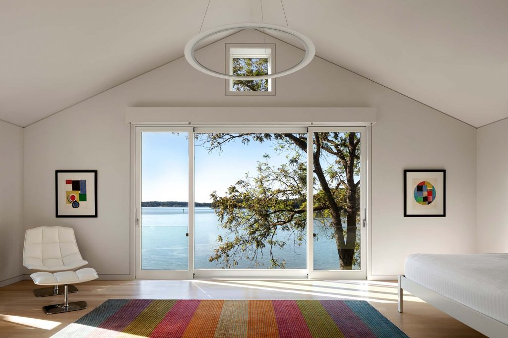 A minimal aesthetic, accentuated by the LED circle chandelier, is in keeping with the homeowners' vision for an interior highlighting art and views.