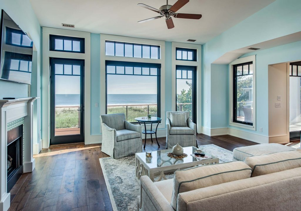 In this light-flooded living room, the eye moves easily from the gorgeous shade of sea foam green on the walls to the matching ocean outdoors.
