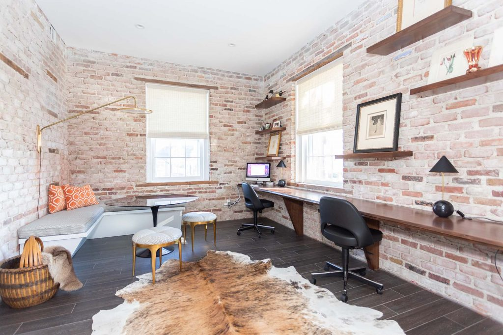 The building's original brickwork led the design in the room that would become the home office.