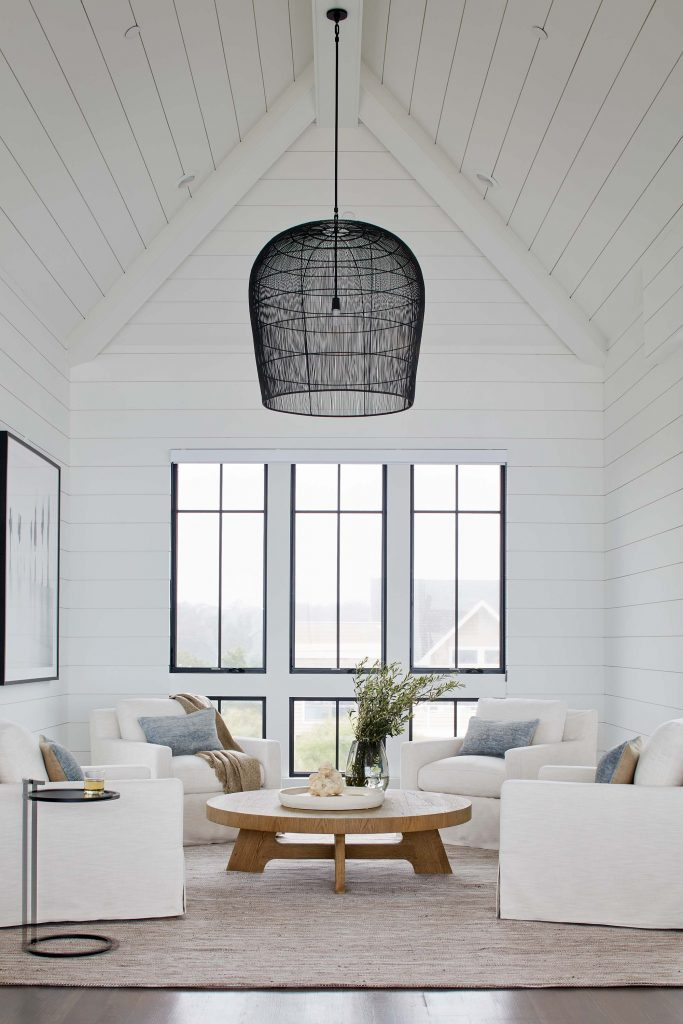 Black trim around the windows and the contemporary black light fixture are softened by the white throughout the rest of the room.