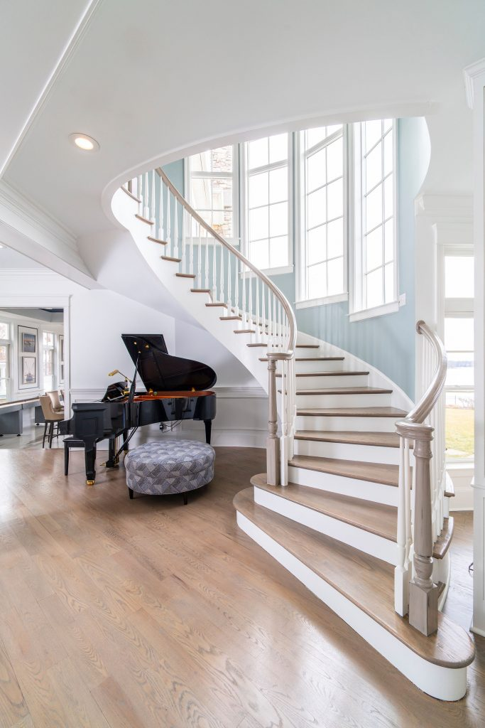The elegant curved handrail on the main level's staircase was sanded several layers down to its original wood finish before being painted a light color.