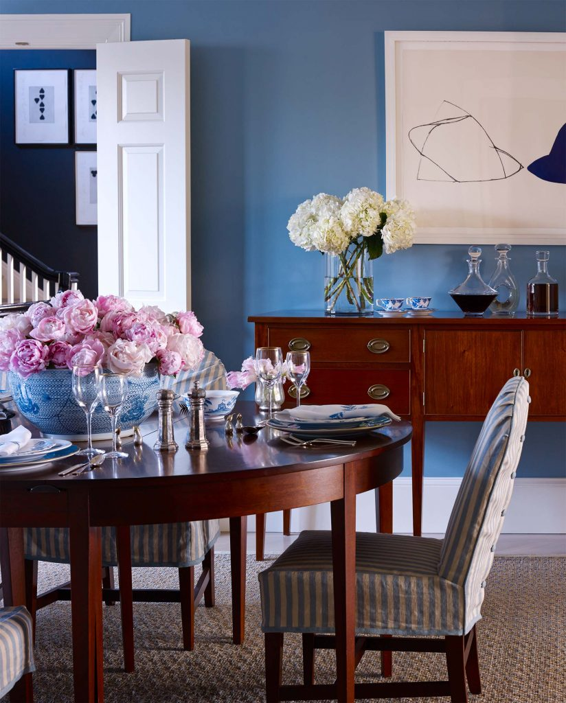 The dining room is painted blue, the home owner's favorite color. The work of art over the console is by Ellsworth Kelly. Photo by Francesco Lagnese.