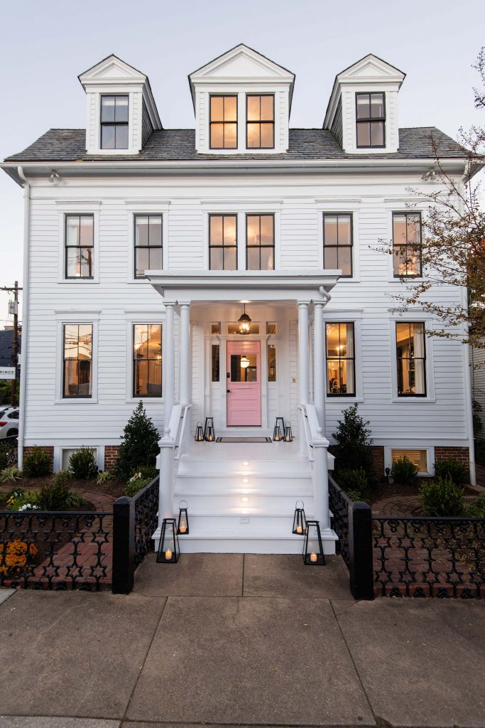 """Prior to its current crisp white paint job, with pink door, this home was a """"painted lady"""" with over four different colors of paint."""