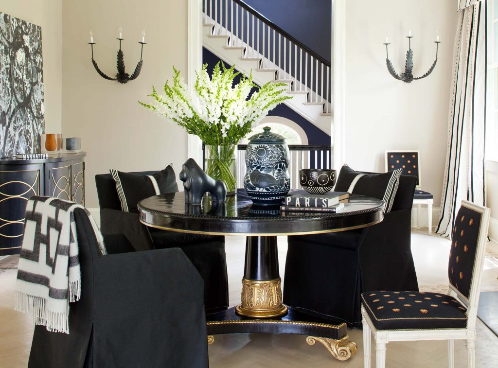 The reception room, centered by a lacquered black table with gold detailing, is steps from the foyer, decked out in black and white diamonds and black and white striped. Photo by Ron Blunt.
