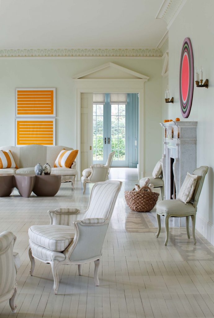 The formal living room opens into the relaxed blue-toned family room, accessed by a pocket door transformed by a period-style pediment. Photo by Ron Blunt.